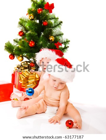 Two babies beside Christmas tree - stock photo