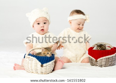 Two babies dressed in white fur with two basket with small kittens