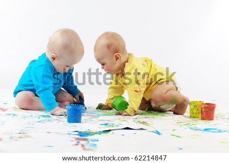 Two babies painting on white background - stock photo