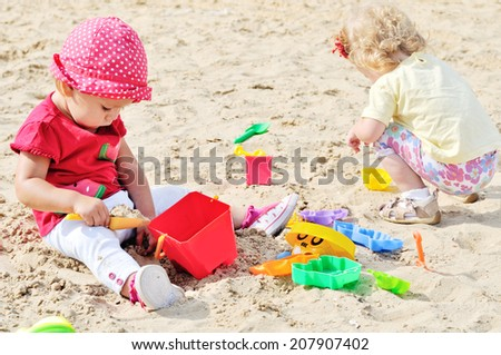 two babies playing toys in sand - stock photo