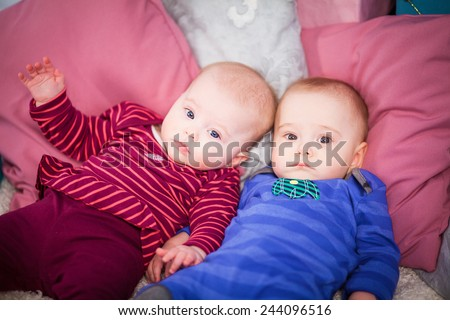two babies (twins) lie on the pillows - stock photo