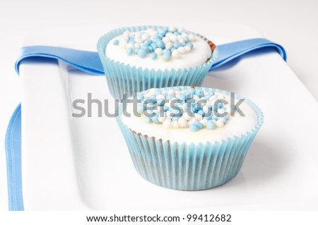Two baby blue cupcakes on a plate with ribbon - stock photo