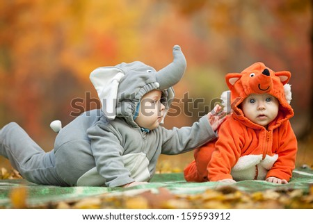 Two baby boys dressed in animal costumes in autumn park - stock photo