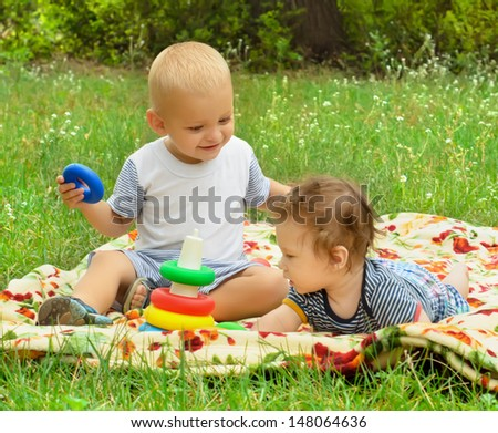 Two baby boys playing together on the lawn in the park - stock photo