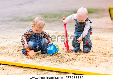 Two baby boys playing with sand in a sandbox - stock photo