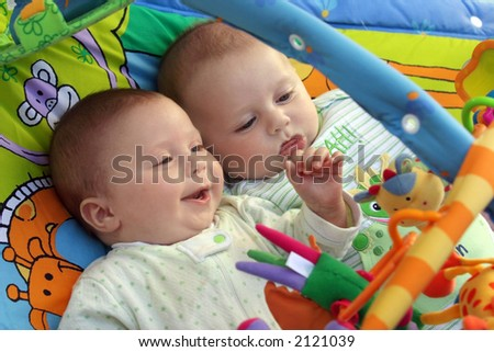 Two baby boys twin brothers playing together - stock photo