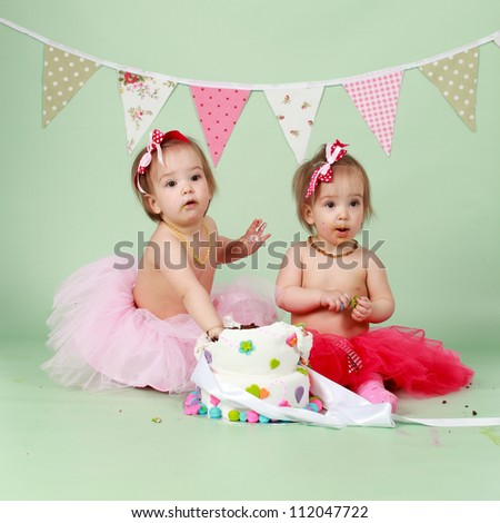 Two baby girl identical twin sisters sitting on green seamless background behind decorated birthday cake wearing red and pink tutus and bunting flags in the background about to break and smash cake - stock photo