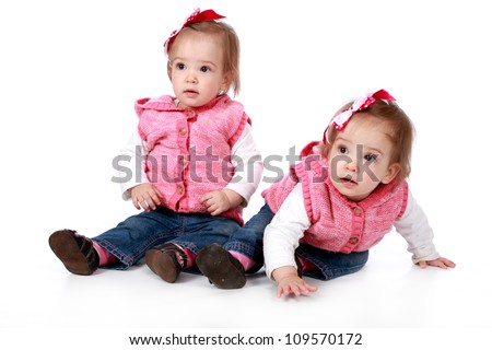 Two baby girl identical twins wearing blue jeans and white top with pink gillet and wearing red and white polka dot ribbon bows in their hair looking cute and adorable on a white seamless background - stock photo