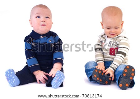 Two baby in beautiful costumes sitting on the floor, looking at each other and smile - stock photo