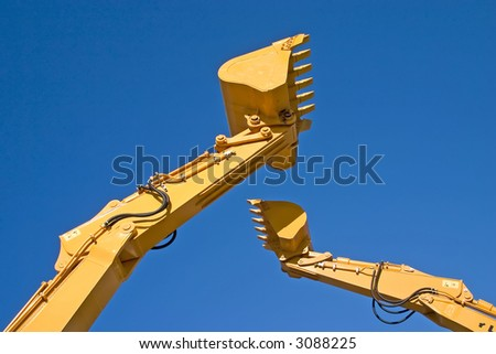 two back hoe diggers high in sky - stock photo