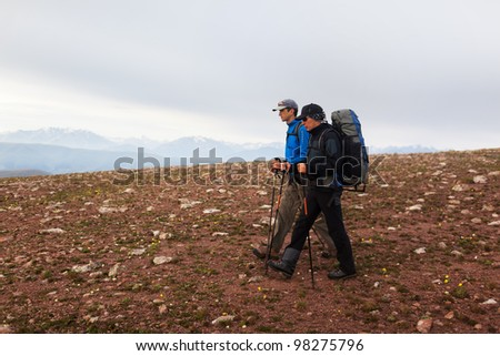 Two backpackers in morning mountains - stock photo