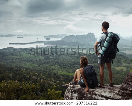 Two backpackers relaxing on top of the mountain - stock photo