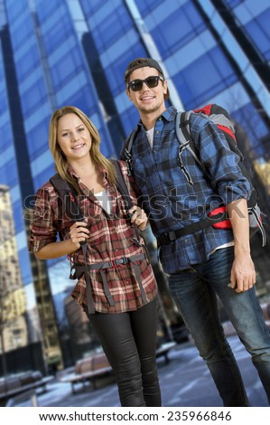 Two backpackers, traveling on a shoestring, posing in front of a tall, glass, skyscraper, - stock photo