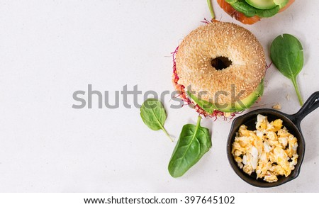 Two Bagels with salted salmon, spinach, beet sprouts, avocado and scrambled egg over white stone surface. Top view - stock photo