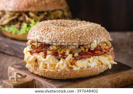 Two Bagels with stew beef, fresh salad, bacon, scrambled eggs and fried onion served on small wooden chopping boards over wooden table.  - stock photo