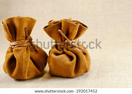 two bags of suede with coins on canvas - stock photo