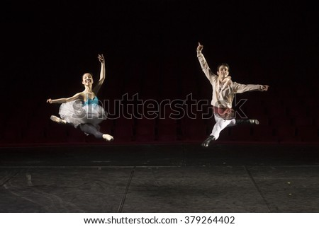 Two ballet dancers jumping high, in air. At theater on a stage. Elevated view.