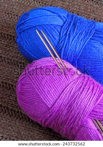 Two balloons of yarn with knitting needles on knitted background - stock photo