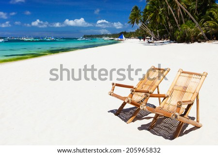 Two bamboo chairs on a beautiful tropical beach with white sand and clear turquoise ocean at exotic island in Philippines - stock photo