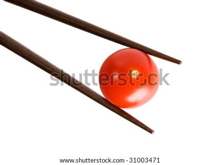 Two bamboo chopsticks holding  cherry tomato on white background - stock photo