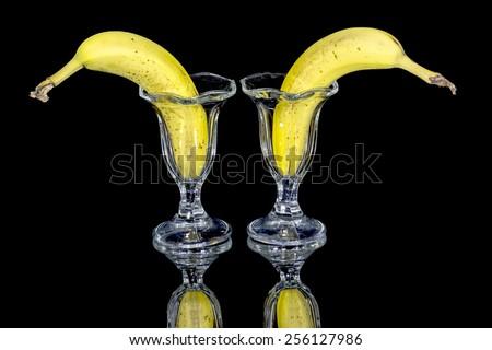 Two bananas in fancy glasses - stock photo