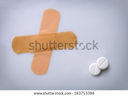two bandaids and two white pills on a white table - stock photo