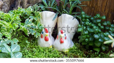 Two bantam's ceramics in little garden. - stock photo