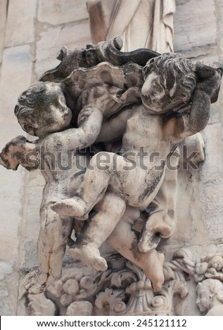 Two bare cherubs sculpture on the wall of Duomo Cathedral (Milano, Italy) - stock photo