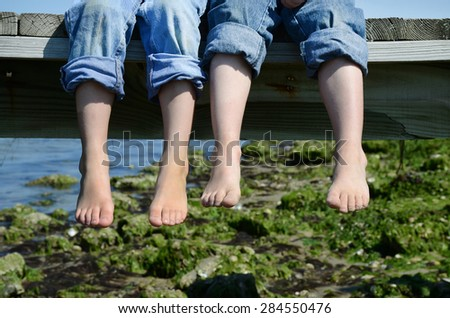 two barefoot boys in jeans sitting on dock - stock photo