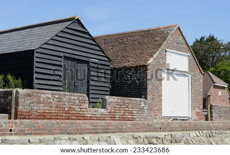 Two barns behind sea wall in village of Bosham. West Sussex. England.  - stock photo