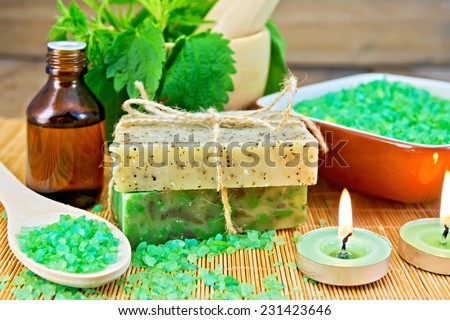 Two bars of homemade soap with twine, bath salt, oil bottle, nettle in a mortar, scented candle on a wooden boards background - stock photo