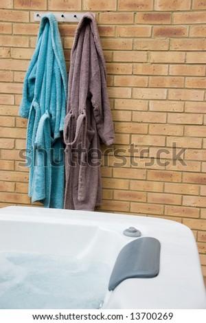 Two bathrobes next to Hot Tub - stock photo