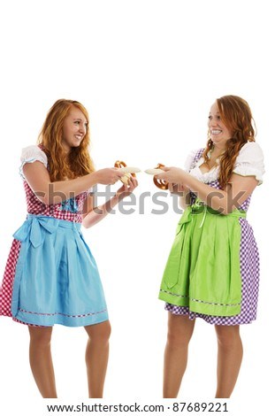 two bavarian dressed girls pulling on veal sausages on white background - stock photo
