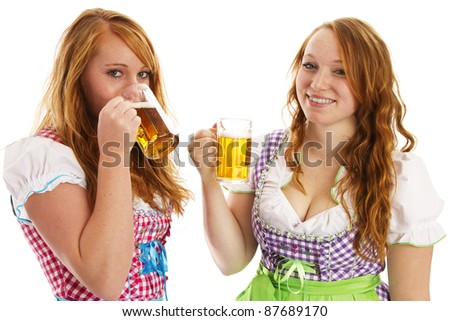 two bavarian girls laughing and drinking beer on white background - stock photo