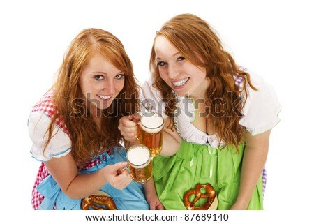 two bavarian girls with beer and pretzels on white background - stock photo