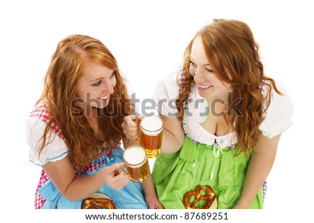 two bavarian women with beer and pretzels on white background - stock photo