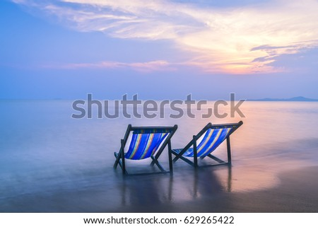 Two beach chairs are located on the beachfront at sunset.