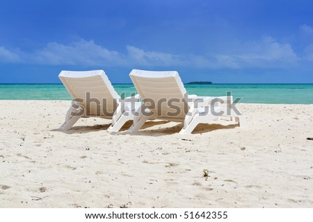 two beach chairs at ocean front - stock photo
