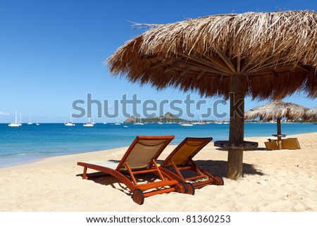 Two beach chairs face the clear waters of the Caribbean sea - stock photo