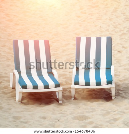 Two beach chairs in sand - stock photo
