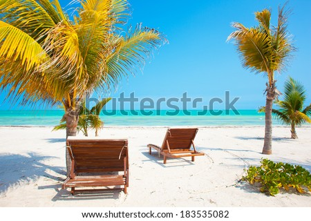 Two Beach Chairs near palm trees on tropical Holbox island Mexico - stock photo