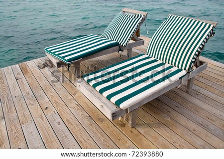 Two Beach Chairs on a Dock Overlooking the Ocean