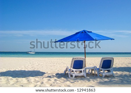 Two beach chairs under a blue umbrella on the white sandy beach at a resort. - stock photo