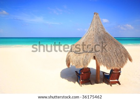 Two beach chairs under the shade of a grass umbrella overlooking a stunning tourist resort beach - stock photo