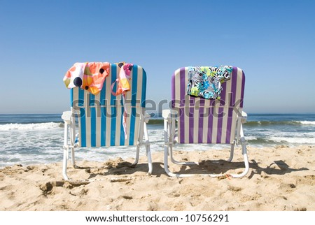 Two beach chairs with bathing suits draped over them insinuate a couple is out for a nude dip in the cool ocean.