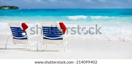 Two beach chairs with Santa hats on beautiful tropical coast with white sand and turquoise water, perfect Christmas vacation banner