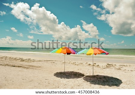 Two Beach Umbrellas on the Sandy Coastline of Anna Maria Island - stock photo