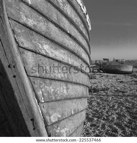 Two beached wooden boats in need of repair. - stock photo
