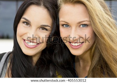 Two beautiful and happy teenage students smiling