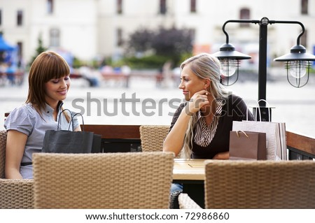 Two beautiful and sophisticated young women friends sitting in a cafe outdoor - stock photo